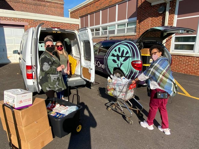 Brandy Buzzuto (left) and Amy Durham of Del-One Federal Credit Union and Dara Dupont of the Rose Hill Community Center unload the donations for the community center's food pantry.