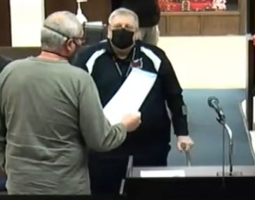 With his back to the camera, Shawnee City Commissioner Bob Weaver reads a mayoral proclamation to longtime KGFF Manager Mike Askins. Mayor Ed Bolt allowed Weaver the honor of presenting the document since his father played a significant role in the radio station's local history.