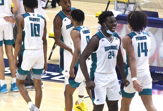Imajae Dodd welcomes his teammates to the sideline for a timeout during UNCW's win over Delaware State on Dec. 23.