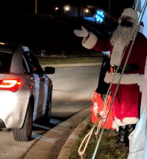 Santa waves at the passing cars during a visit to Springfield Lake Park earlier this month.