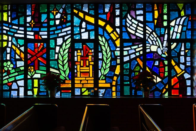 "The Irene Jones Memorial Window inside First Lutheran Church is designed to remind viewers that Jesus is alive and ruling in his world. According to church information on the windows, the first symbol is a statement of Christ's ascension into heaven with a ""P"" symbol touching both the earth, in green, and heavens, in blue. In the middle are symbols representing Christ's rulership with a throne of God and two palm branches of victory. An angle with a trumpet shows the closing words of the Second Article, ""he shall come again to judge the living and the dead."" The window was a gift from Jones' daughter, Sallee Lee."