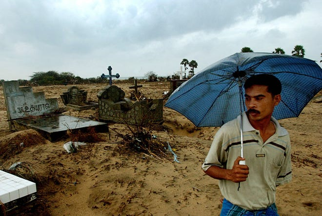 A Sri Lanka man stands by graves blasted by tsunamis in Akkaraipattu, Sri Lanka, on  Jan. 4, 2005. At least 137,321 people were killed in 11 countries in southern Asia and East Africa from the massive earthquake and tsunamis on Dec. 26.
