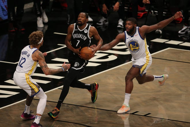 Nets forward Kevin Durant drives against Warriors forwards Kelly Oubre Jr., left, and Eric Paschall, right, during the first quarter Tuesday night at the Barclays Center.