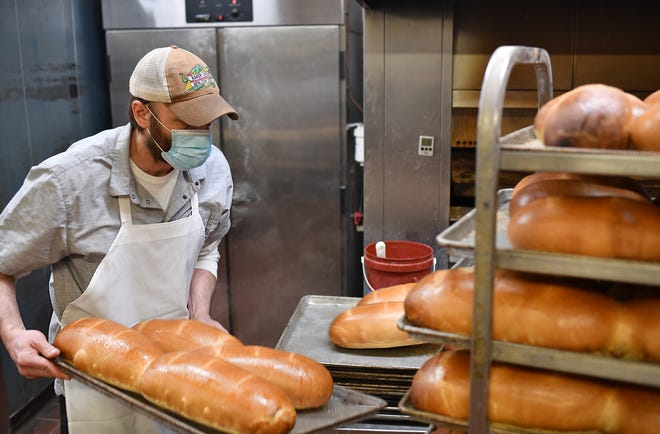 Casey Griswold stows fresh baked rye bread just out of the oven at European Bakery & Pastry on Millbury Street, which he owns with his brother Brett Griswold.