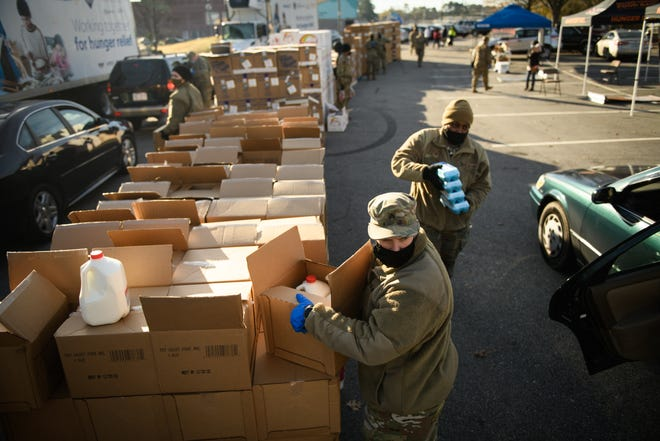 Action Pathways Second Harvest Food Bank of Southeast NC distributes food to 500 Cumberland County households on December 23, 2020, at the Smith Recreation Center. Airmen from the North Carolina Air National Guard and soldiers from the North Carolina Army National Guard help load food into vehicles at the drive thru food distribution event.