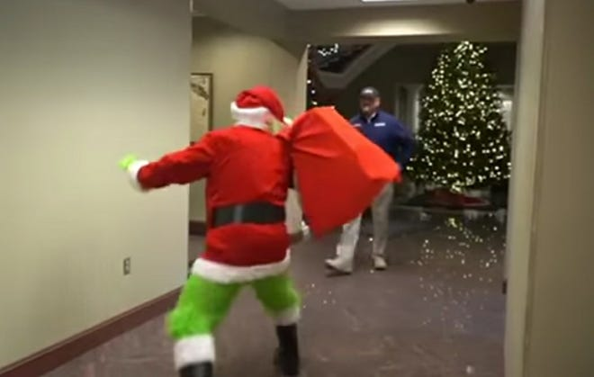 Robeson County Sheriff Burnis Wilkins closes in on The Grinch on Sunday night as the dastardly fellow tries to make off with Christmas gifts in the Lumberton Town Hall. The Grinch is being held in detention on bond until his heart grows three times larger.