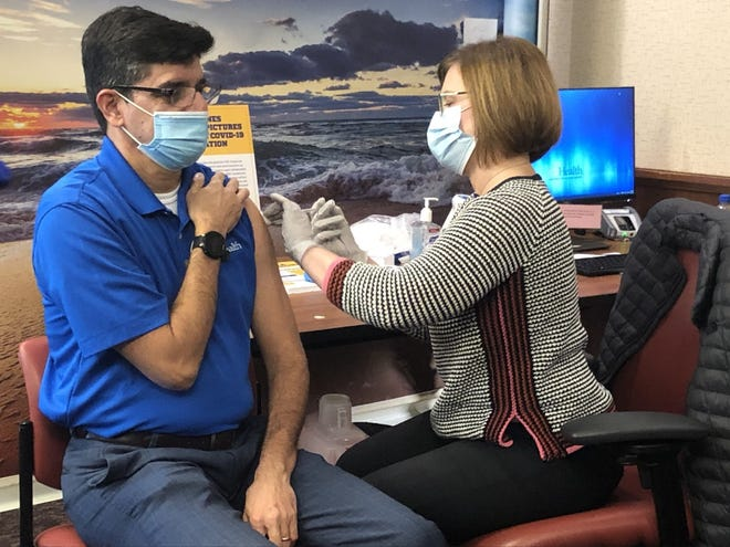 Dr. Michael Lauzardo, director of UF Health's Screen, Test & Protect program, is given a COVID-19 vaccine Wednesday morning. UF Health was given a batch of Moderna vaccines Tuesday night, just days after the medical system began vaccinating health care workers with the Pfizer vaccine.
