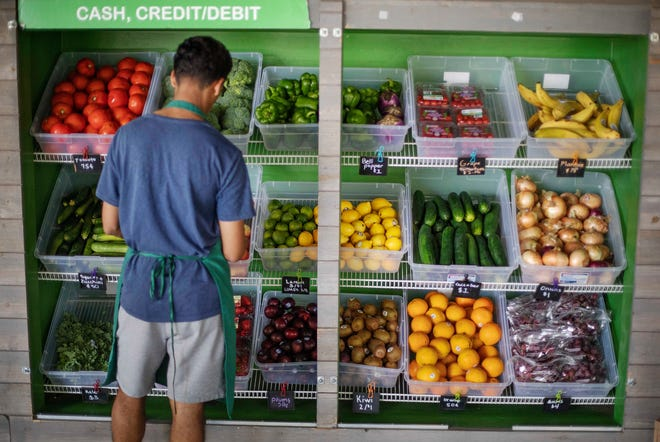 A worker stocks a produce stand at a metro station in Atlanta. Throwing away food is throwing away money. And with most wasted food winding up in landfills, it's not great for the environment, either.