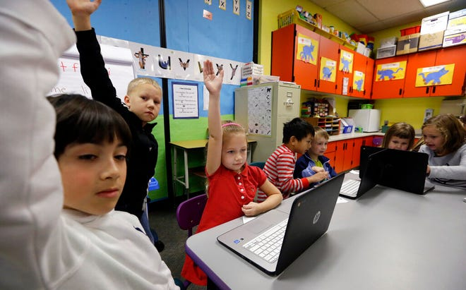 In this 2015 photo, students raise their hands during their weekly computer science lesson at an elementary school.