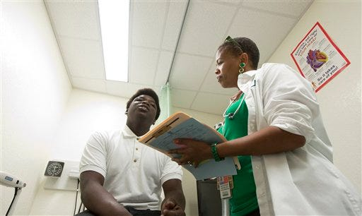 A doctor conducts an examination of a student at a clinic in a Miami high school.