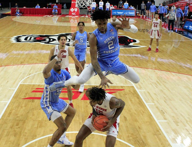 North Carolina's Caleb Love hurdles N.C. State's Manny Bates as North Carolina's Garrison Brooks, left, defends during Tuesday night's game at PNC Arena.