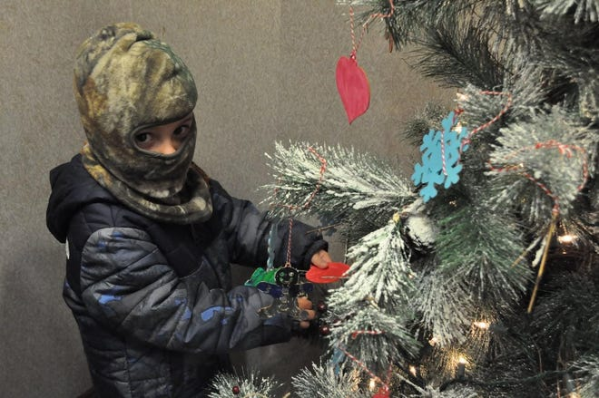 Knox Manin hangs an ornament on the tree at the First National Bank of Dennison.