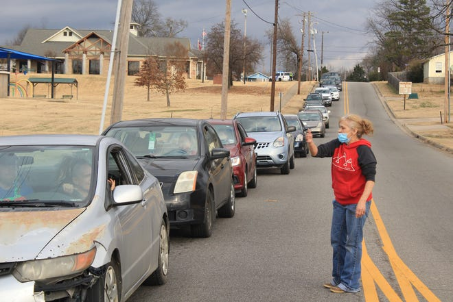 Volunteer Belinda McNew gives directions to drivers on Greenwood Road on Wednesday, Dec. 23, 2020, at Antioch For Youth & Family's pop-up giveaway at Martin Luther King Park in Fort Smith. Antioch Director Charolette Tidwell said she expects Fort Smith's 2020 poverty rate to spike from the impact of COVID-19.