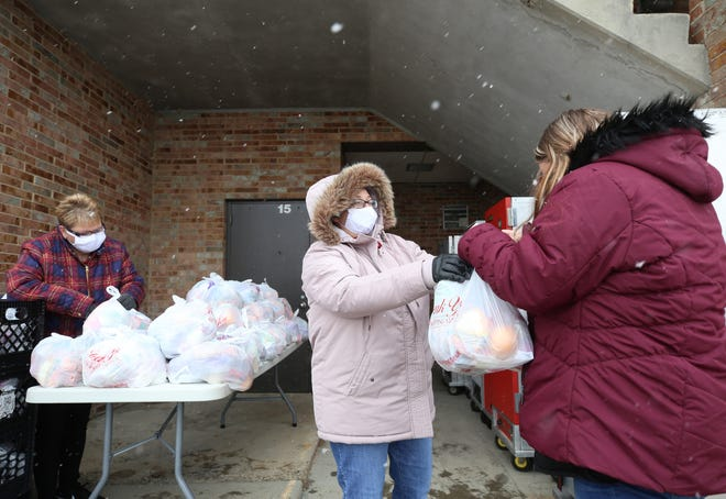 Deidre Rath, a head cook with the South-Western City School District, arranges food bags while cook Jennifer Meyerin hands food to Amanda Dewalt during a food pickup at Grove City High School on Dec. 16.