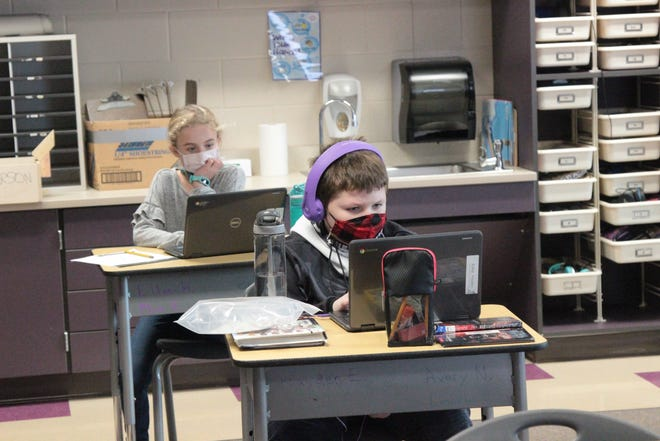 Toll Gate Elementary fourth-graders Hayden Estep, front, and Ellie Hartley work on assignments with district-issued laptops. District officials said the ongoing use and expansion of technology in the classroom and through virtual learning will be a priority in 2021.