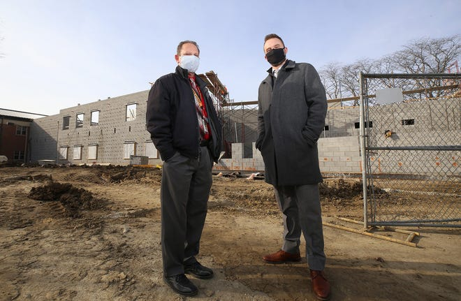 Jason Sherman (left), Delaware City Schools facilities and transportation director, and Dempsey Middle School principal Daniel Bartha stand in front of the addition under construction at Dempsey.