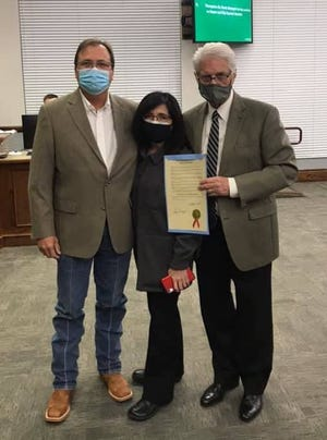 Former Waxahachie mayor and City Council member Kevin Strength (left) is accompanied by his wife, Jean, as they are presented with a proclamation from Mayor David Hill honoring Strength for his 10 years of City Council service during Monday night's meeting.