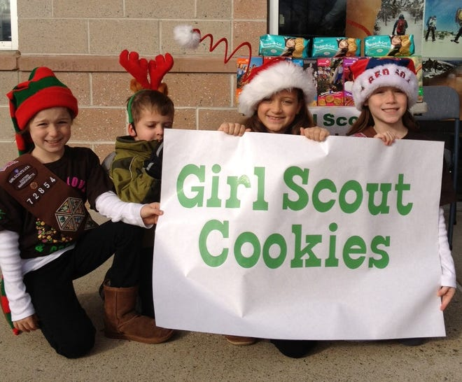 Marlborough Girl Scouts celebrated their 100 years of Girl Scouting in Marlborough on Dec. 20. Pictured are Marlborough Girl Scouts Angelina Tureio, Abby Dwiczyk and Sofia Turieo with a helper in 2012 on the 100th anniversary of Girl Scouts of the USA.