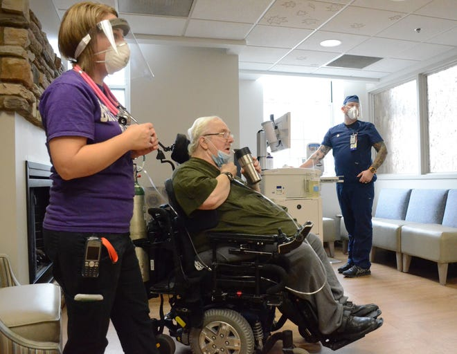 Veteran Donald Madden of Battle Creek, takes a drink after becoming the first veteran at the Battle Creek VA to receive the COVID-19 vaccine. Nurses Amanda Smith of Delton, left and John McCash of Kalamazoo, administered the vaccine.