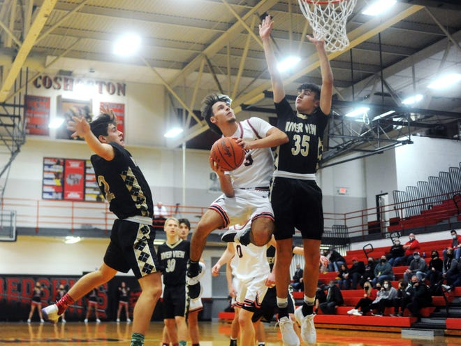 Coshocton's Nathan Fauver goes through the lane against the defense of River View's Drew Ireland, left, and Owen Emig during the Redskins' 45-42 win on Tuesday night at The Wigwam.