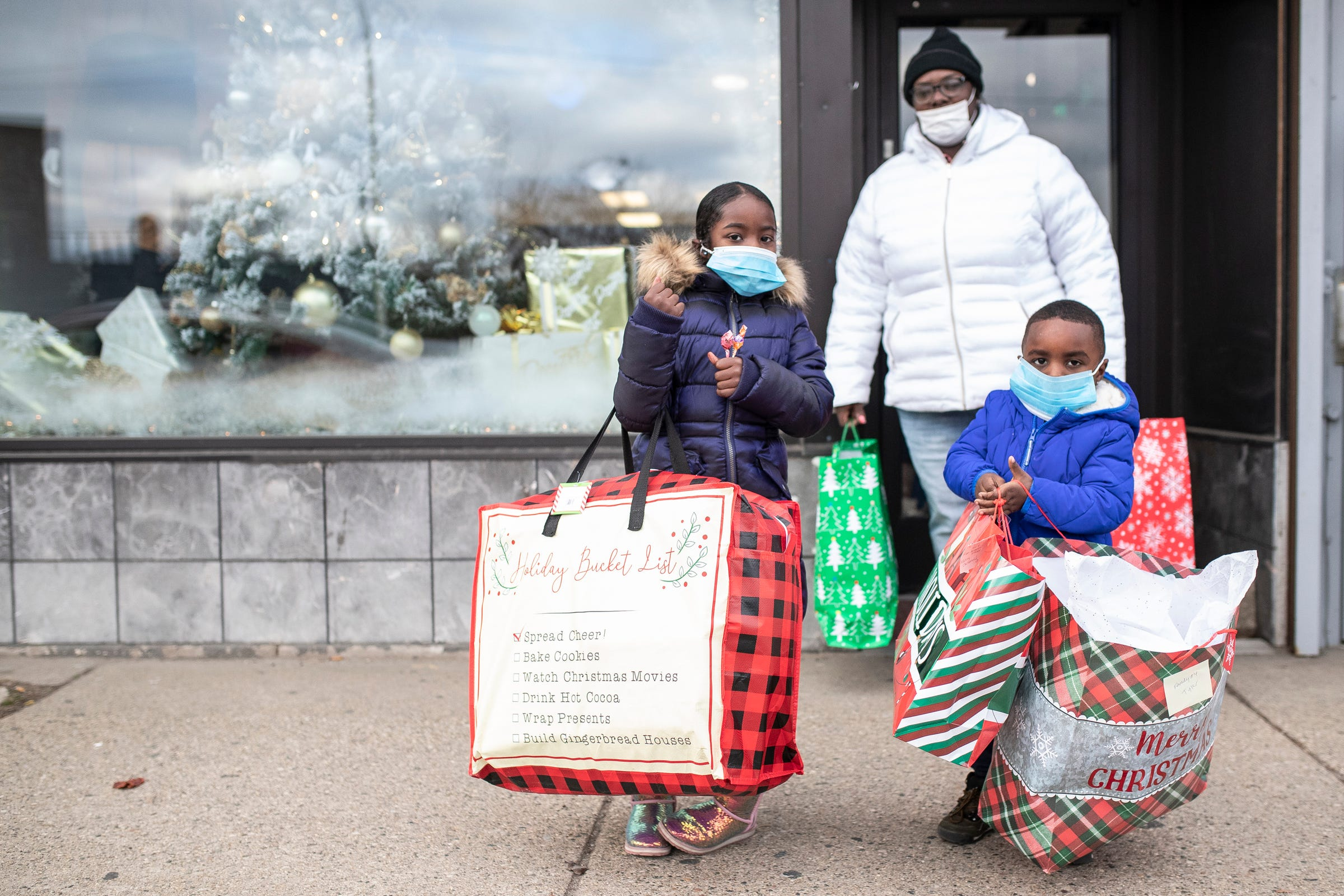 Savannah Cowart, 6, her brother Tyler Cowart, 4, and mother Monika Chester, all of Ecorse, walk out of Dream Rich Art Museum in Detroit after receiving gifts on Tuesday, Dec. 22, 2020.