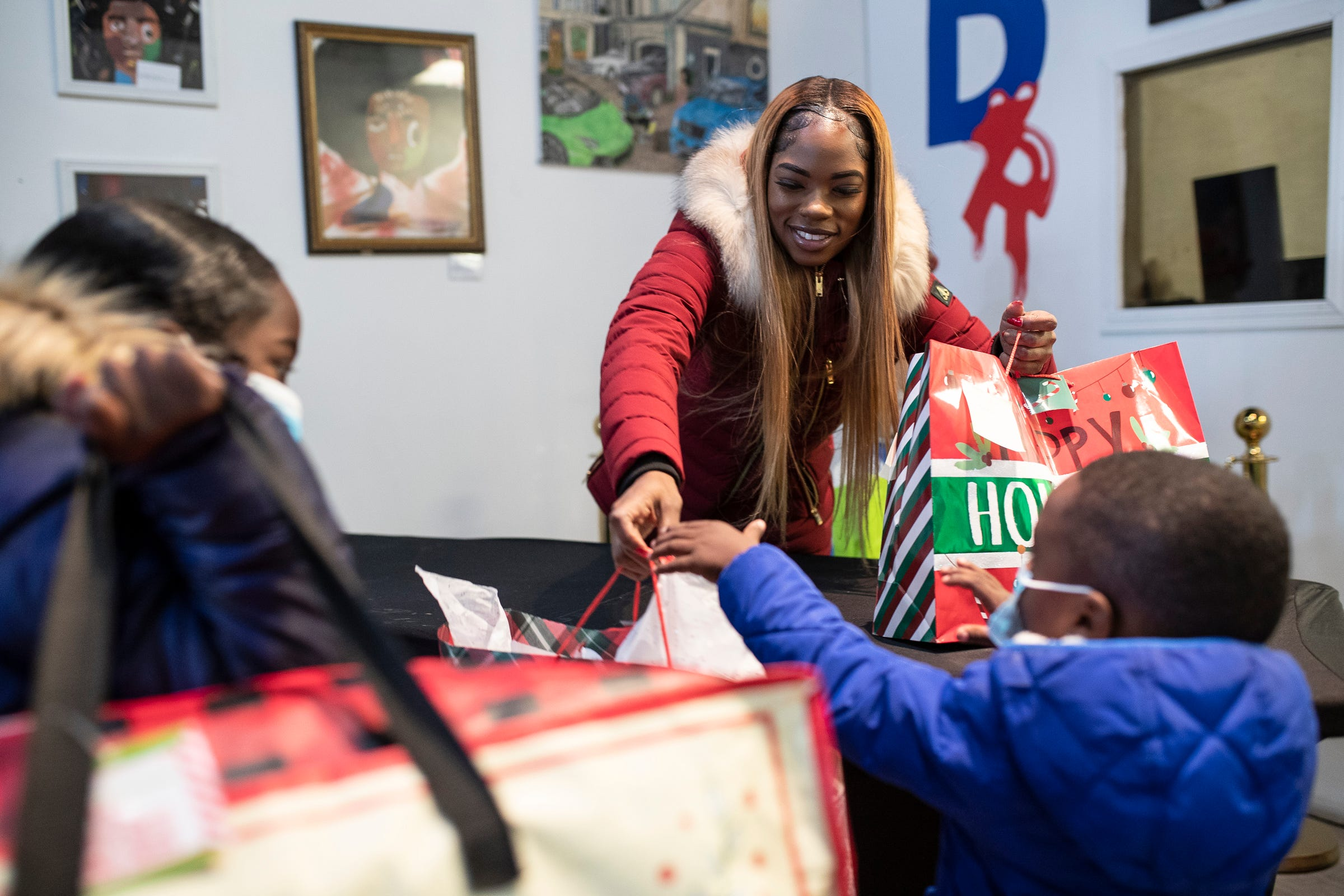 Tia Russell, founder of Take My Hand, hands gifts to Tyler Cowart, 4 and his sister Savannah Cowart, 6, both of Ecorse at Dream Rich Art Museum in Detroit on Tuesday, Dec. 22, 2020.