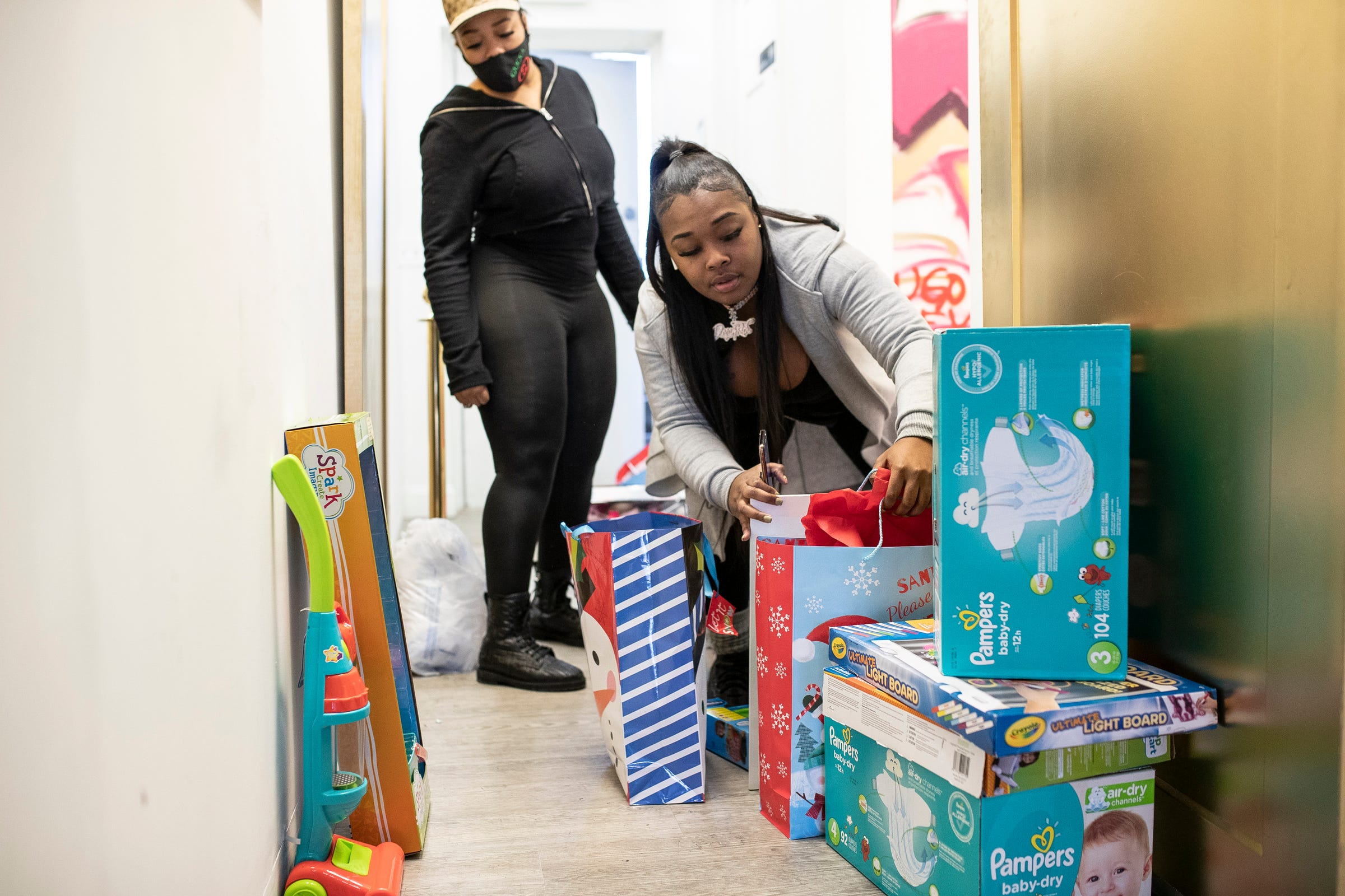 Darylynn Mumphord, owner of the Dream Rich Art Museum, center right, and Bonnie Parker, owner of Silk Hair Company, wrap and sort gifts for families at Dream Rich Art Museum in Detroit on Tuesday, Dec. 22, 2020.