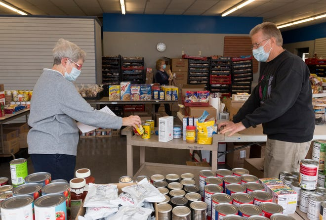 Evansville Emergency Food Pantry Consortium administrator Sylvia Deters, left, and volunteer John Smither, right, pull food for a client at the Nativity Eastside Pantry located at 1304 South Green River Road Wednesday morning, Dec. 23, 2020.