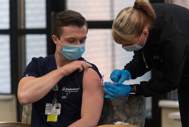 Deaconess Health System's Registered Nurse Casey Goldsberry receives one of the first public Moderna COVID-19 vaccines from Certified Medical Assistant Michelle Webb in Henderson, Ky., Wednesday morning, Dec. 23, 2020.