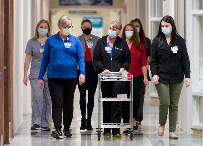 Deaconess Henderson Hospital Certified Medical Assistant Michelle Webb pushes a cart with the Moderna COVID-19 vaccine down a hallway before administering the vaccine for the first time in Henderson, Ky., Wednesday morning, Dec. 23, 2020.
