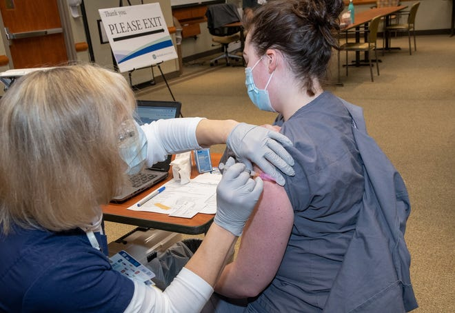 Diana Horn, of Fairfield Medical Center Employee Health & Wellness, administers the COVID-19 vaccine to Arriana Rifenburg, of the Observation Unit. Arriana was the first staff member to receive the vaccine at Fairfield Medical Center.