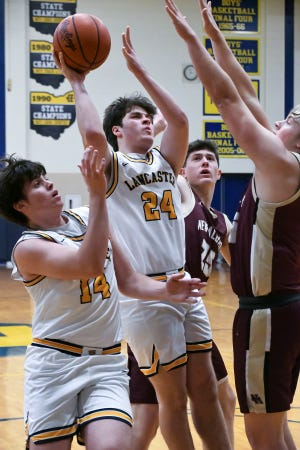 Lancaster junior Sam Finck attempts to shoot the ball over the out stretched arms of a New Albany defender Tuesday night at LHS. The Golden Gales won 67-42 and improved to 5-0.