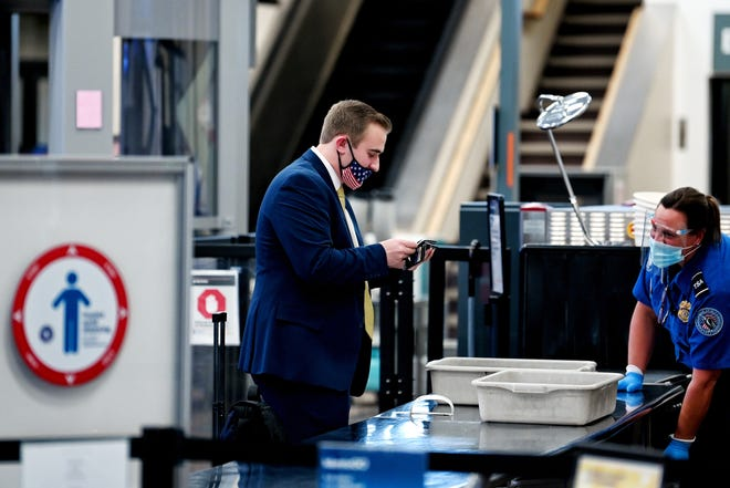 Joshua Wagner, left, goes through security before boarding a flight home on Wednesday, Dec. 23, 2020, at the Capital Region International Airport in Lansing.