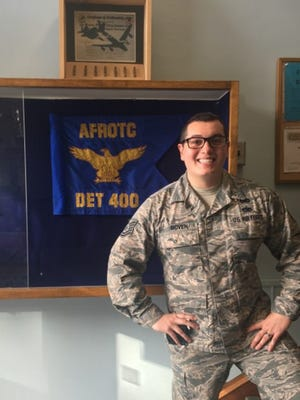 "Technical Sgt. Vince Boven poses beside the Air Force ROTC Detachment 400 guidon at Michigan Technological University in Houghton, Michigan. ""Boven is an amazing noncommissioned officer and will be an outstanding officer,"" said Lt. Col. Joseph Pulliam, AFROTC Detachment 400 commander."