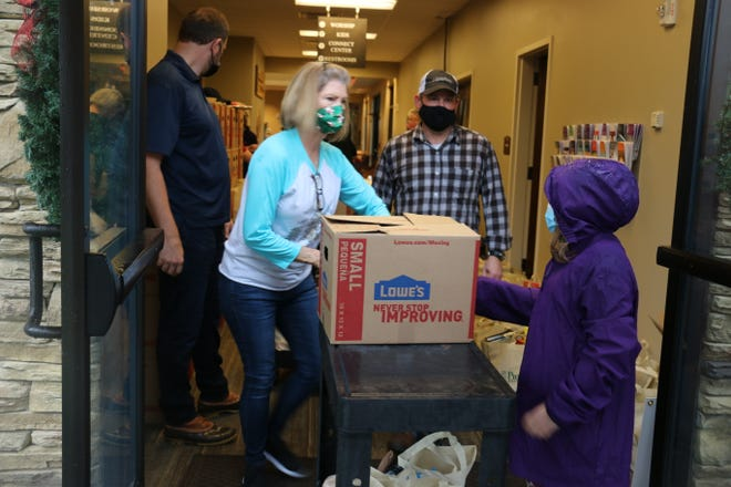 Volunteers load food onto carts to deliver to trunks on Dec. 12, 2020, in Nolensville, Tennessee, at the Nolensville Food Pantry.