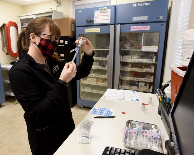 Licking County Health Department registered nurse Michelle Hughes draws up doses of the Moderna COVID-19 vaccine. The county began administering the first local doses of the vaccine, which is stored cold in vials, to EMS workers on the morning of Wednesday, Dec. 23, 2020.