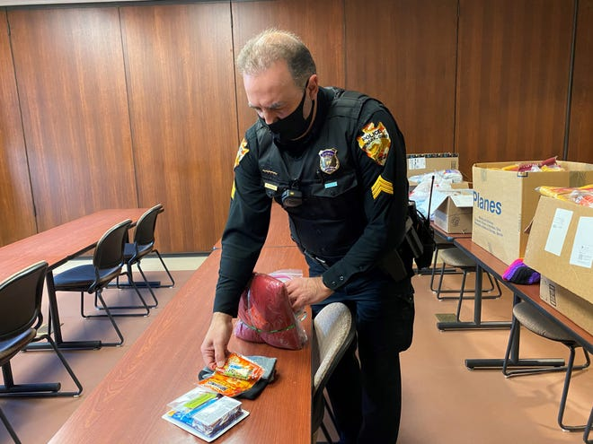 Newark Police Sgt. Bert Gliatta shows items inside bags, which the agency plans to distribute to those in need while on service calls, at Newark's police station on Wednesday Dec. 23, 2020. Newark Division of Police recently partnered with Starfish Assignment of Licking County to gather donations of items for the area's homeless population.