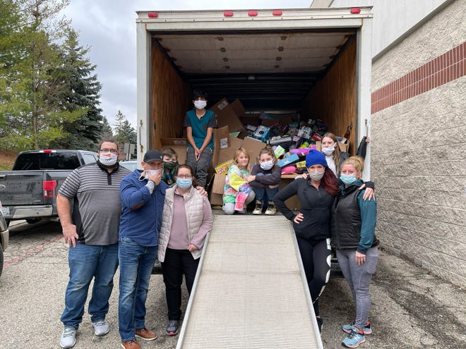 """Sherise Assad (in blue cap) with friends after loading a truck with $100,000 worth of toys for children in need this Christmas. Assad was recognized with a """"Rise to the Occasion Award"""" by the Huron Valley Chamber of Commerce."""