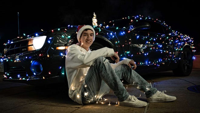 Tyler Kamholz poses with his car that he decorated for Christmas.