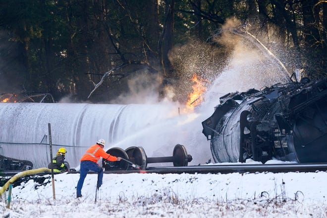 A firefighter sprays foam on a burning, derailed train car Tuesday, Dec. 22, 2020, in Custer, Wash. Officials say seven train cars carrying crude oil derailed and five caught fire north of Seattle and close to the Canadian border.