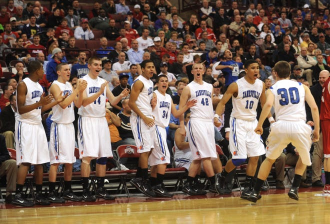 Zanesville's Tanner Gibson (10) and Jordan Bouterse (30) and the Zanesville bench celebrate after a three by Gibson bounced off the rim and in after Gibson was fouled.