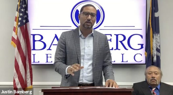 Attorney Justin Bamberg, standing, speaks at a news conference as plaintiff Jethro DeVane, seated at right, listens, Tuesday, Dec. 22, 2020, in Orangeburg, S.C.