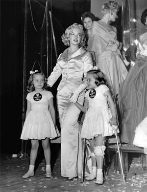 Actress Marilyn Monroe with 1958 March of Dimes poster children Linda and Sandra Solomon, and the 14th annual March of Dimes fashion show in 1958.