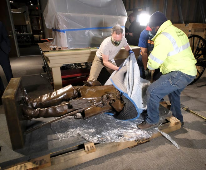 Dale Kostelny, left, Exhibit Production Manager for the Virginia Museum of History and Culture helps Michael Sullivan, center, and Tyrone Price, right, with Hutchinson United Rigging in Washington, DC, uncover the statue of Robert E. Lee that had been moved from the U. S. Capitol to the Virginia Museum of History and Culture in Richmond, Va. Tuesday, Dec. 22, 2020.