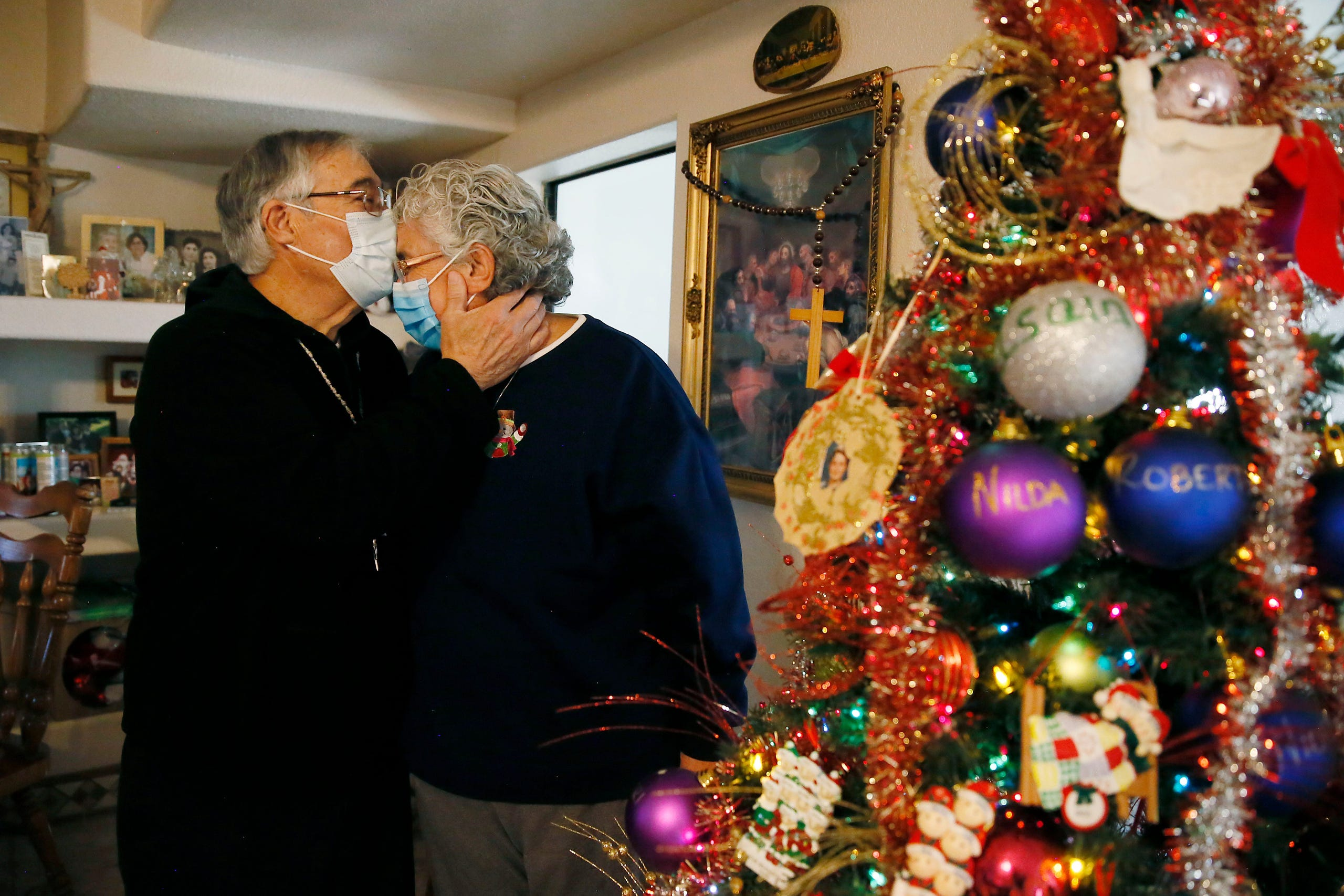 Roberto Mata gives his wife Mary Alice a kiss on the forehead by their Christmas tree Wednesday, Dec. 16, 2020, at their home in Chaparral, New Mexico. He survived COVID-19 after spending 47 days at the Hospital of Providence Memorial Campus in El Paso earlier this year. The Mata family says they are grateful for their health and for his recovery.MAIN_Mata Family Covid 19 001