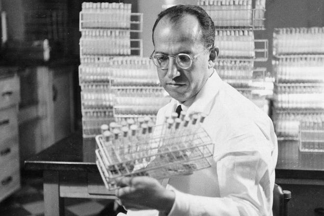 Dr. Jonas Salk, developer of the polio vaccine, holds a rack of test tubes in his lab in Pittsburgh on Oct. 7, 1954.