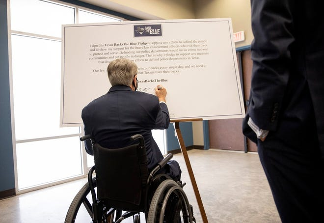 """Gov. Greg Abbott signs a """"Texas Backs the Blue Pledge""""  in September at the Austin Police Association. Abbott has called for legislation that would allow the state to take over the Austin Police Department in response to city officials reducing APD's budget."""