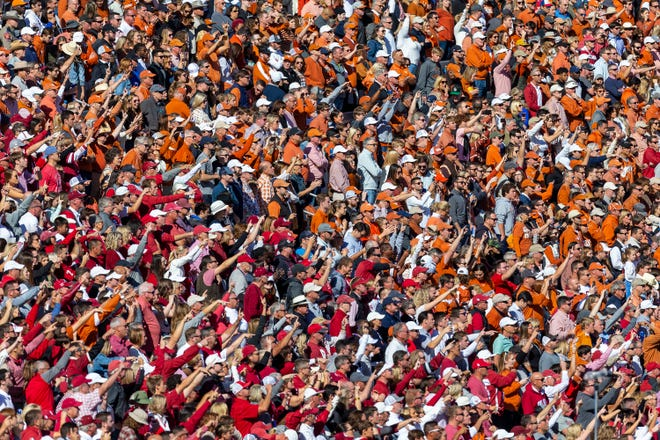 """Passions run high as Texas and Oklahoma fans yell for their teams during the Red River Rivalry game in 2019 at the Cotton Bowl in Dallas. The universities and their rivalry are rich with tradition, but one tradition is under fire: UT's school song, """"The Eyes of Texas,"""" has become a flash point amid social justice protests."""