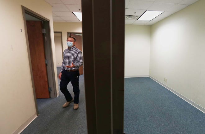 Keith Stahl, director of operations and residential services for Community Support Services, walks through the expanded space acquired by CSS to service the area's homeless population in Akron.