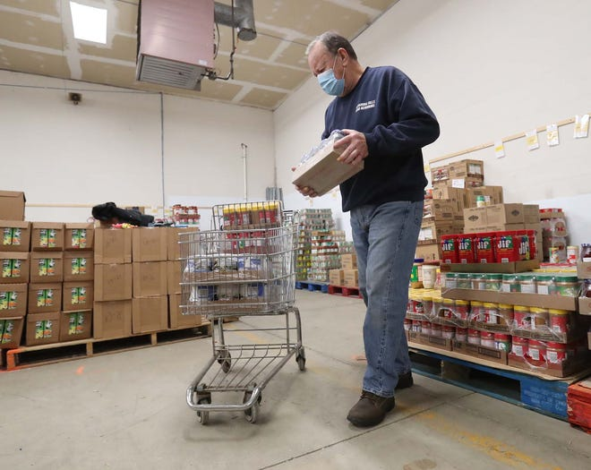 Mike Amos, a volunteer at Good Neighbors Cuyahoga Falls, packs food for distribution on Dec. 22. Amos has been in charge of ordering and picking up food for the local food pantry since the coronavirus pandemic struck in March.